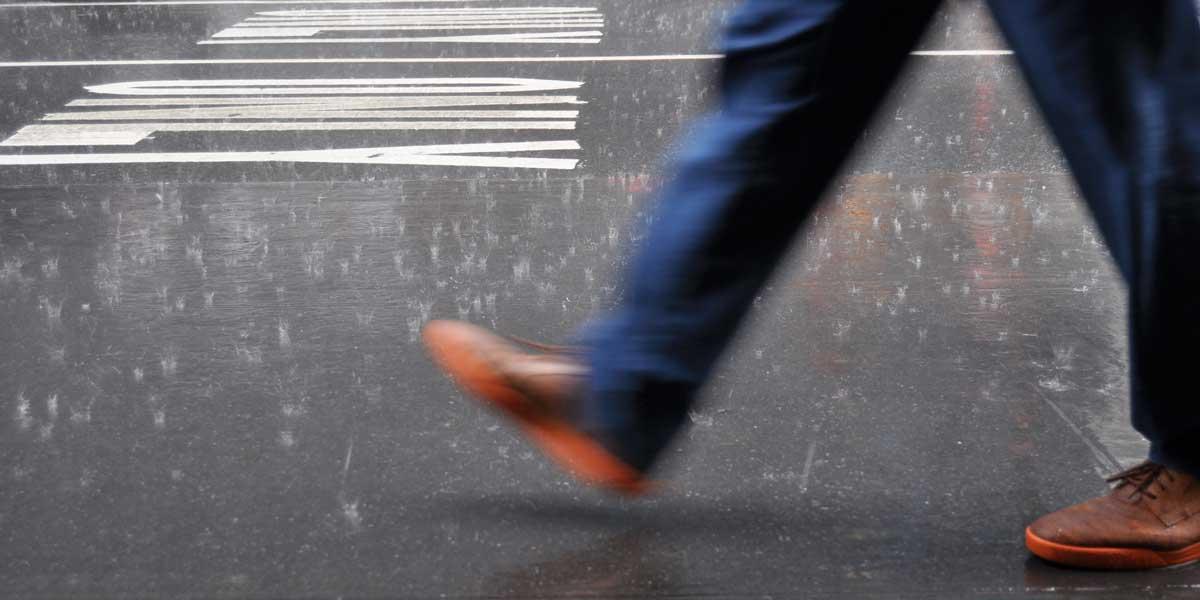 persona dando un paso sobre la carretera