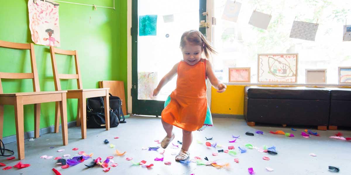 niña con un vestido naranja jugando en la guardería