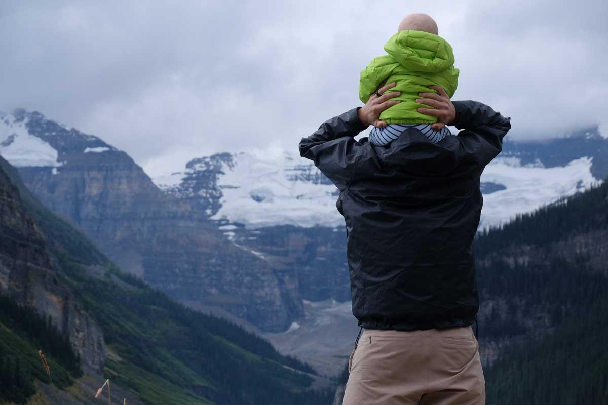 Papá con su hijo a cuestas en la montaña nevada