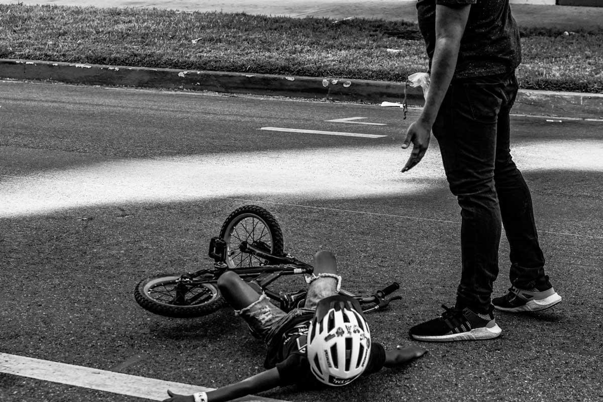 Niño en bicicleta en el suelo con su papá