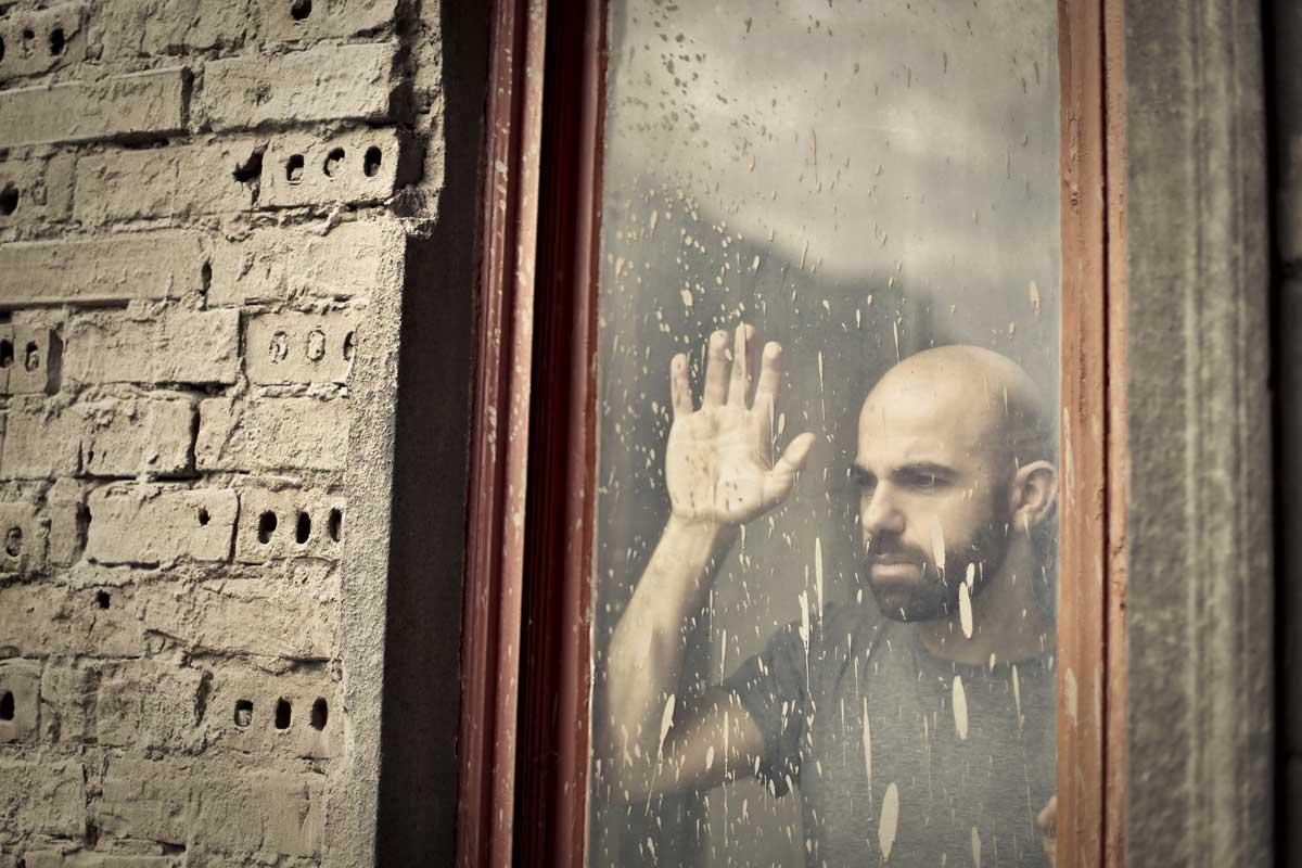 persona triste mirando por la ventana