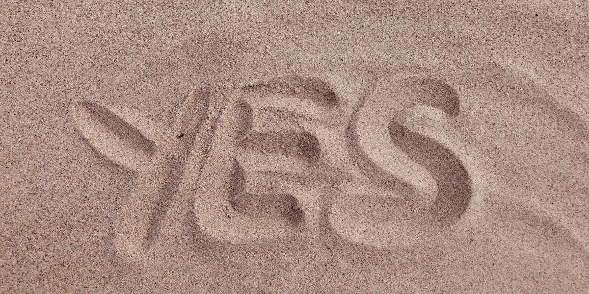 yes dibujado sobre la arena