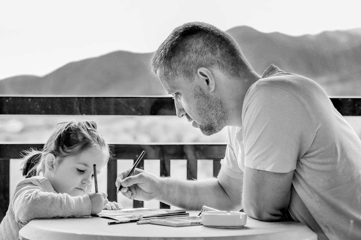 Padre y hija con un lápiz en la mano y escribiendo sobre una mesa
