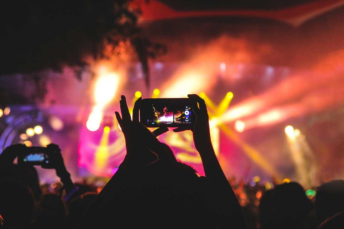 concierto con todos haciendo fotografías.