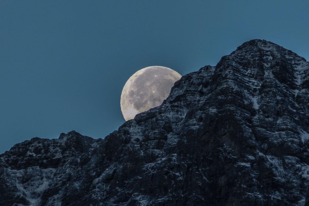 Luna apareciendo detrás de una montaña