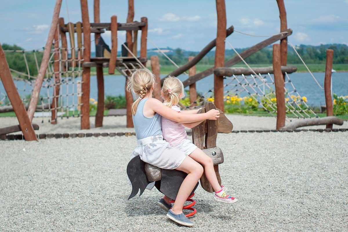 niñas jugando sobre un caballito en un parque infantil