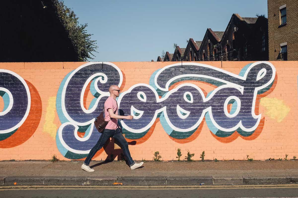 calvo caminando delante de un graffiti