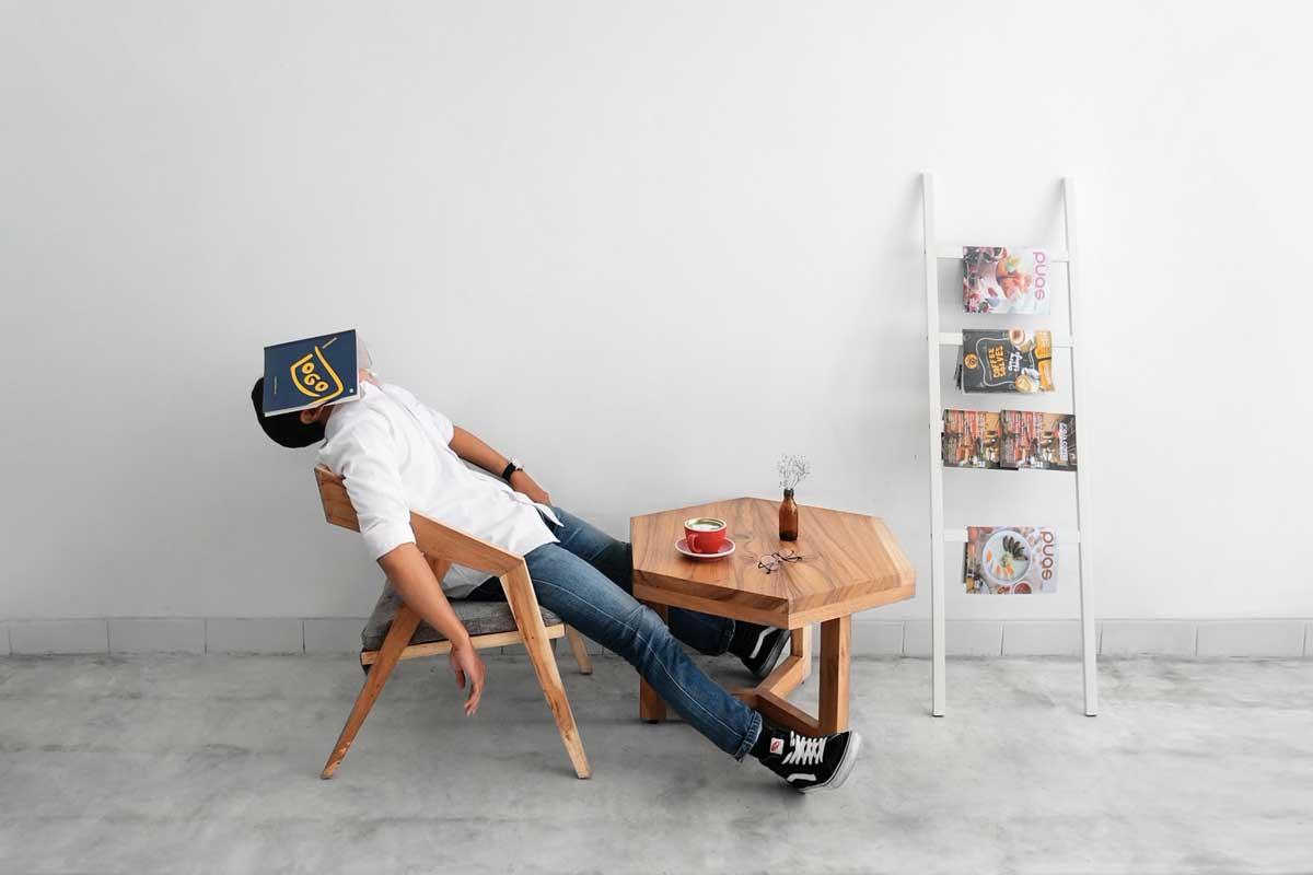 señor dormido en una silla y leyendo una revista