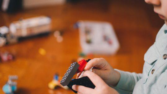manos de niños jugando con un Lego