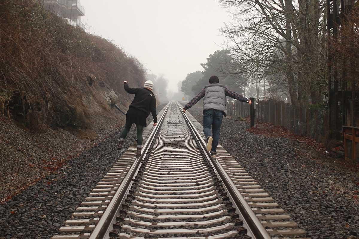 dos jóvenes saltando en la vía del tren